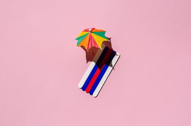 ピンクの砂浜の太陽の傘とカラフルなビーチタオル