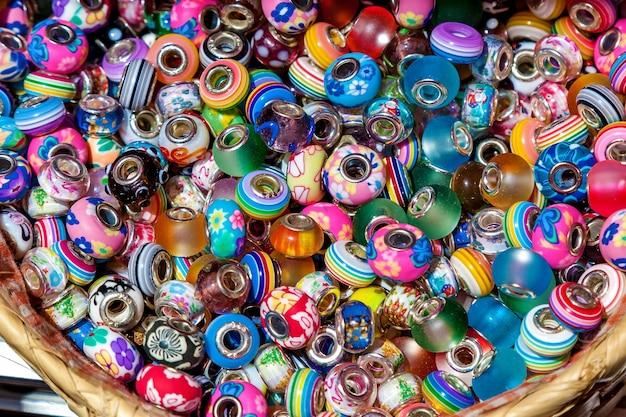 그릇에는 다양한 장식품이 달린 화려한 구슬이 놓여 있습니다. 다양한 재료와 모양의 기념품, 몰타.