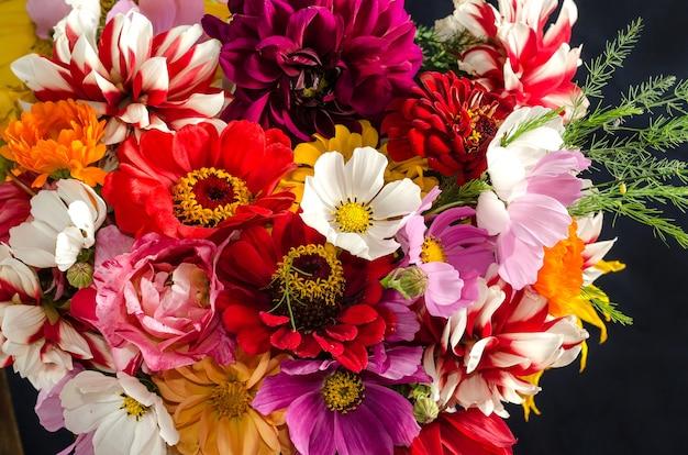 黒い表面に庭の花のクローズアップのカラフルな美しい花束。