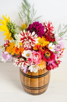 Colorful beautiful floral bouquet of garden flowers in a vase on a white surface.