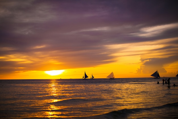 Colorful beautiful sunset with sailboat on the horizon in boracay island