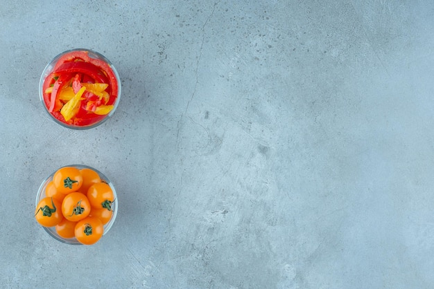 Colorful bell pepper salad and cherry tomatoes in glass cup.