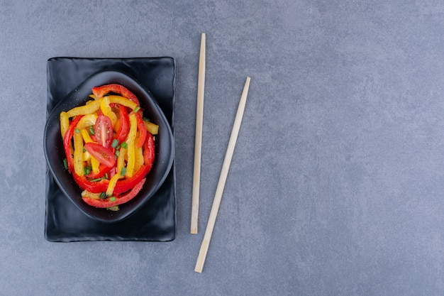 Colorful bell pepper salad with cherry tomatoes on blue surface
