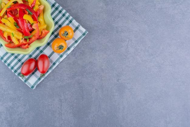 Красочный салат из болгарского перца с помидорами черри на синей поверхности