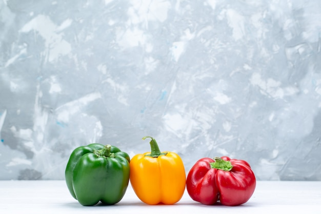 Colorful bell-peppers lined on light