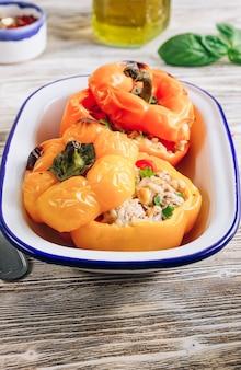 白い木製の背景に肉、米、野菜を詰めたカラフルなピーマン。セレクティブフォーカス