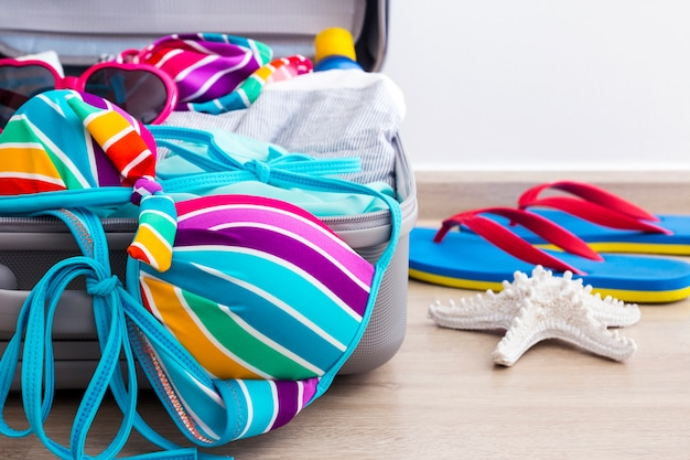 Colorful bikini and clothes in luggage on the laminate floor