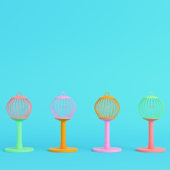 Colorful bird cages on bright blue in pastel colors