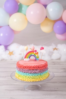 Colorful birthday cake. rainbow cake with pastel colored balloons. birthday celebration.