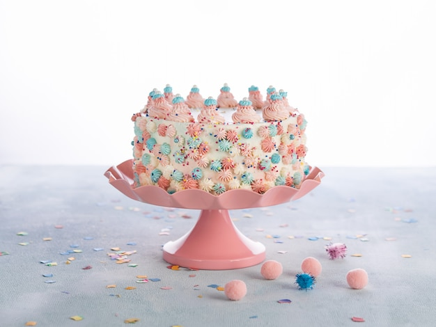 Colorful birthday cake with sprinkles over white.