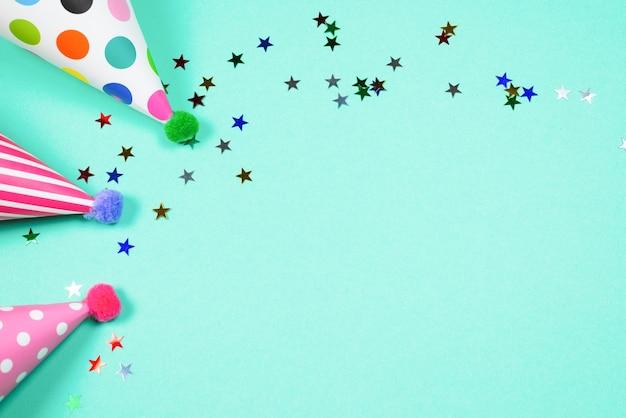 Красочные шапки дня рождения на синем фоне. вид сверху. скопируйте пространство.