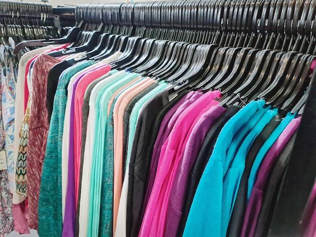 Красочные женские блузки на вешалке для продажи в магазине одежды