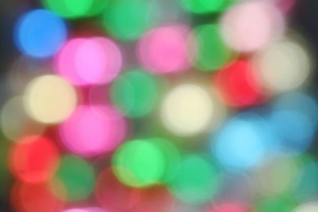 カラフルな背景のボケ味。クリスマスツリーの照明、低いキー。