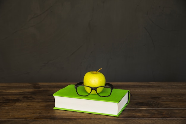 Libro colorato con occhiali e mela sulla scrivania