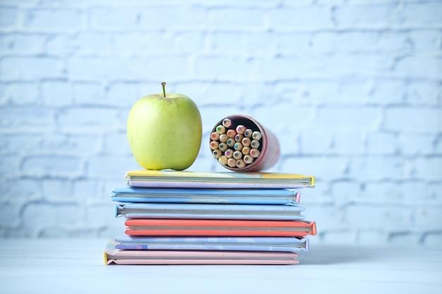 테이블에 다채로운 책, 사과 및 색 연필