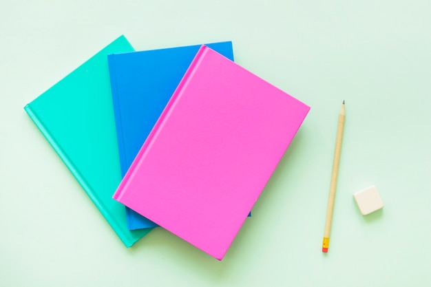 Colorful books with pen and eraser