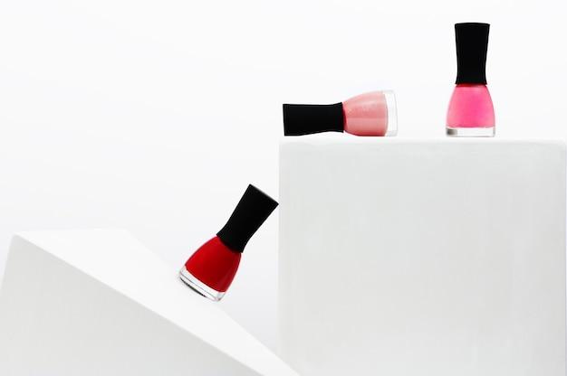 다채로운 매니큐어 병은 흰색 배경에 기하학적 스탠드에 거짓말을 하고 서 있습니다. 매니큐어 및 페디큐어용 미용 제품. 여성 화장용 바니시 팔레트. 공간을 복사합니다.
