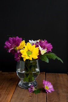 Colorful bouquet of chrysanthemum flowers in glass, dark background.