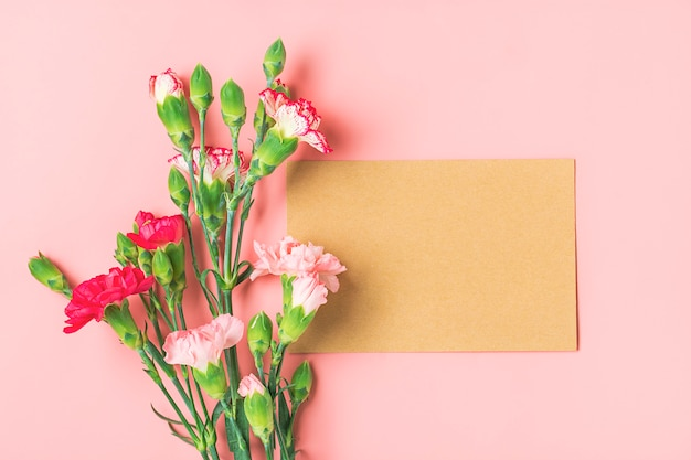 Colorful bouquet of different pink carnation flowers, white notebook on pink background