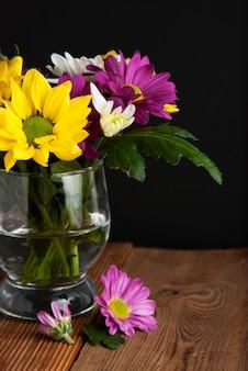 Красочный букет цветов хризантемы в стекле, темный