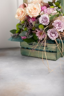 Colorful bouquet of various flowers in a wooden vintage box. women's day background. vertical image, side view, copy space
