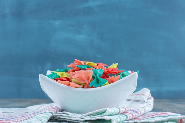 Colorful bow tie pasta in the bowl, on the tea tower , on the marble background.