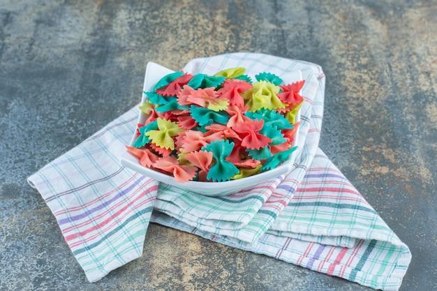 Цветная паста с галстуком-бабочкой в чаше, на чайной башне, на мраморной поверхности.