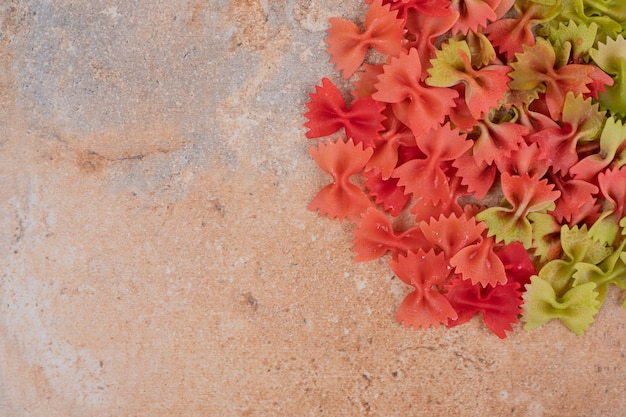 大理石の背景にカラフルな蝶ネクタイパスタ。高品質の写真