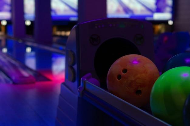 Красочные шары для боулинга на подставке в боулинг-клубе