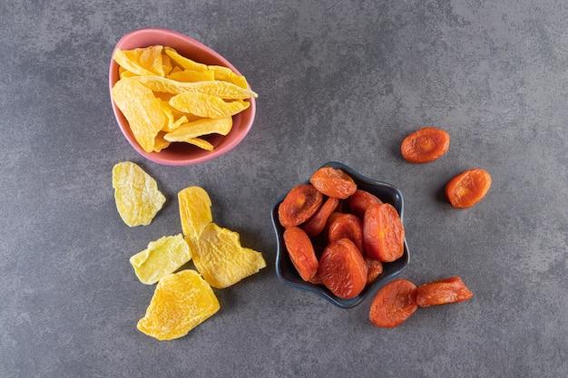 Красочные чаши сушеных ананасов и абрикосов на каменной поверхности.