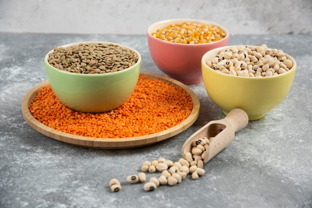 Colorful bowls of various uncooked beans, lentils and corns on marble table surface.