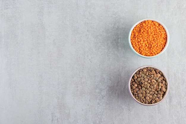 Colorful bowls with raw lentil and buckwheat on stone background.