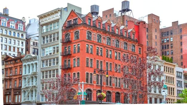 窓と非常階段のあるカラフルなレンガ造りの建物。屋上に水が溜まる。ニューヨーク、アメリカ