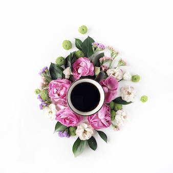 Colorful bright image made of leaves, roses and petals with coffee cup on white