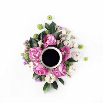 白のコーヒーカップと葉、バラ、花びらで作られたカラフルな明るい画像