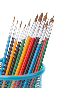 Colorful brushes for painting close up. in the blue basket.