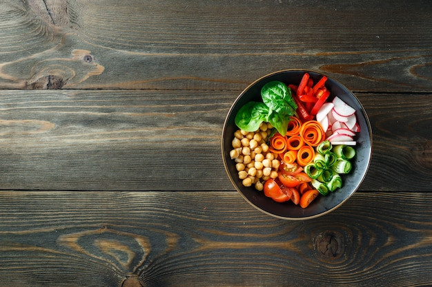 Colorful buddha bowl with chickpeas, carrots, tomatoes, cucumbers, radish and peppers on wooden table. vegetarian salad. top view. copy space.