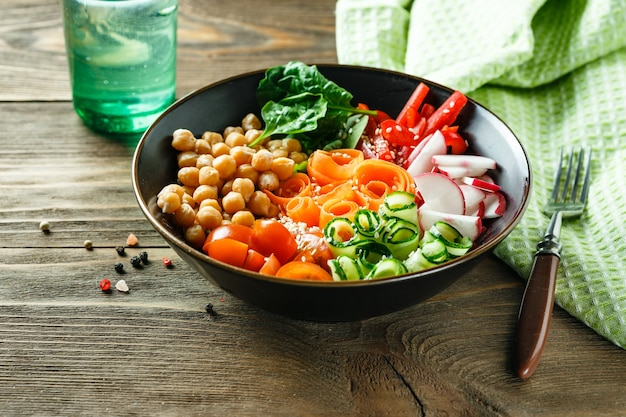 Colorful buddha bowl with chickpeas, carrots, tomatoes, cucumbers, radish and peppers on wooden table. vegetarian salad.