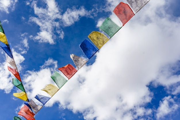 Colorful buddhist prayer flags with vivid color use as tailsman for safety travel in tibetan on blue sky background
