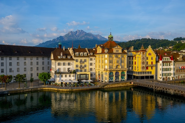 スイスのルツェルンの山々に囲まれた川の近くのカラフルな建物
