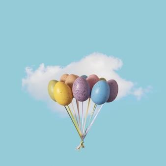 Красочная связка воздушных шаров пасхальных яиц с белым облаком на голубом небе.