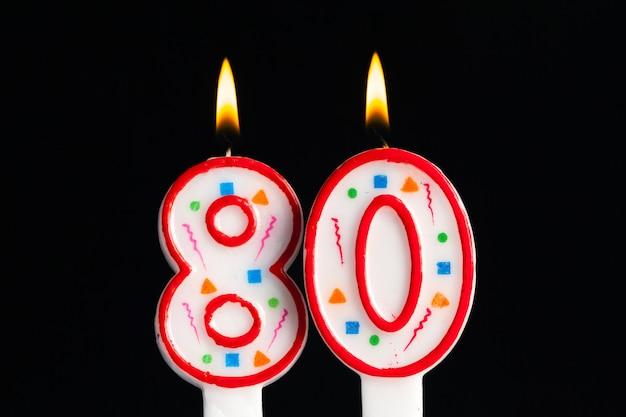 Colorful burning birthday candle  on dark