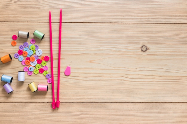 Colorful button and spool with pink knitting needles on wooden backdrop