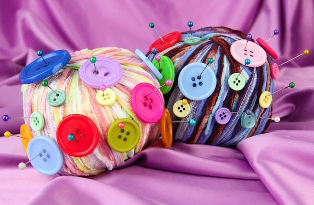 컬러 패브릭 배경에 다채로운 단추와 여러 가지 빛깔의 양모 공