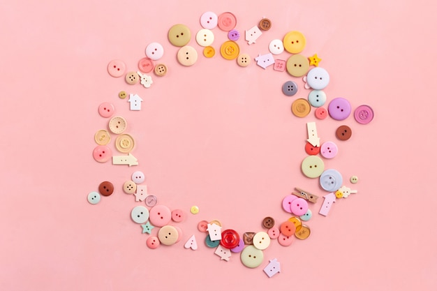 Colorful buttons on pink. flat lay, sewing concept. rounded frame composition