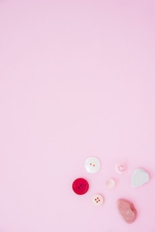 Colorful buttons and soap on the corner of the pink background