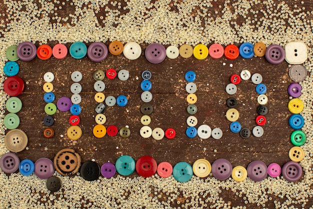 Colorful buttons vintage for sewing hello word shaped around little yellow buttons on a wooden rustic desk