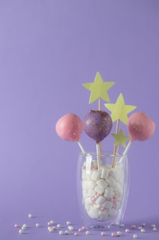 Colorful cake pops in a glass with marshmallows on a purple wall with sprinkles. festive, birthday wall
