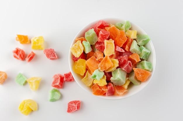 白で隔離の白いボウルにカラフルな砂糖漬けの果物。