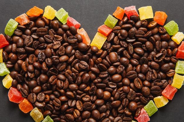 デザインのために黒い背景に分離された茶色のコーヒー豆とハートの形でカラフルな砂糖漬けの果物。休日のコンセプトである2月14日の聖バレンタインデーカード。広告用のスペースをコピーします。